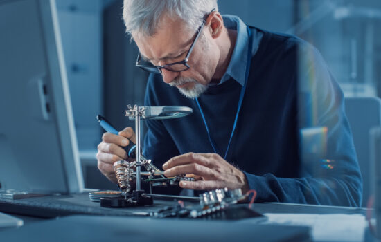 Electronics Maintenance Engineer Soldering Motherboard, Microchip and Circuit Board, Looking through Magnifying Glass, Consults Personal Computer. Electronics Repair and Testing